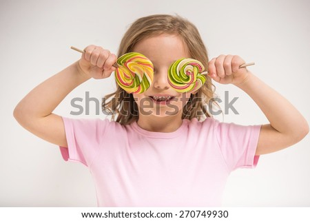 Having fun with candies. Cheerful little girl covering eyes with lollipops and smiling. - stock photo