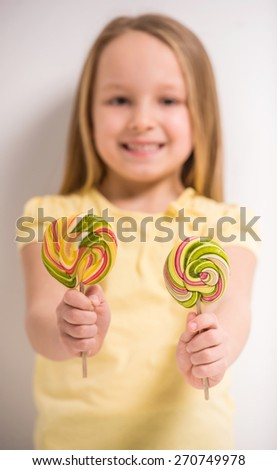 Having fun with candies. Cheerful little girl holdong lollipops and smiling. Focus on lollipops. - stock photo