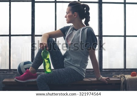 Having had a good workout, a fit, healthy woman takes a few moments to relax and look out at the city below while sitting on a bench holding her water bottle. Next to her, a ball and towel. - stock photo