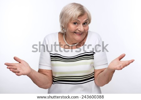 Having no clue. Cropped image of elderly woman shrugging her shoulders with clueless expression while standing against white background - stock photo