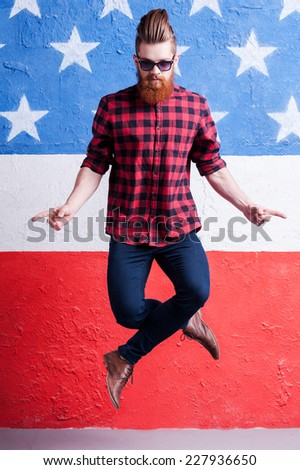 Having no equal. Handsome young bearded man in sunglasses jumping against American flag - stock photo