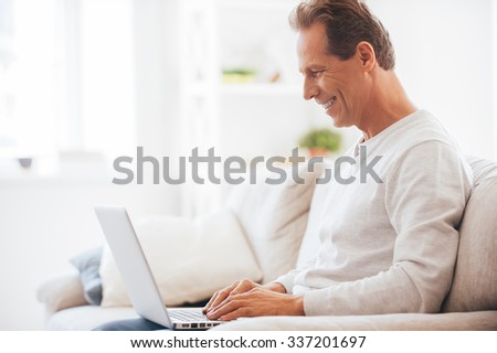Having opportunity to work anywhere. Side view of mature man working on laptop and smiling while sitting on the couch at home