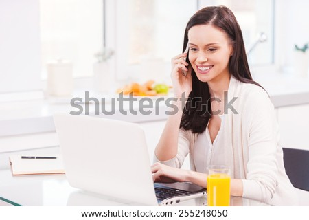 Having opportunity to work everywhere. Attractive young woman working on laptop and talking on the mobile phone while sitting in the kitchen  - stock photo