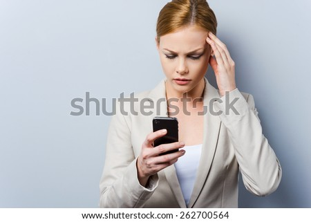 Having some troubles. Beautiful young businesswoman holding mobile phone and touching her face while standing against grey background - stock photo
