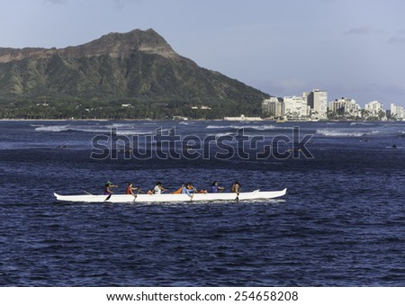 Hawaii-August 5, 2014:  Outrigger Canoe, with Diamond Head and surfers in the background, enjoy swells and winds generated by Category 1 Hurricane Iselle, 300 miles off shore. - stock photo