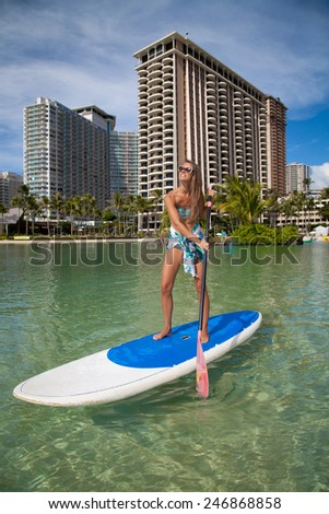 Hawaii beach lifestyle woman paddleboarding in bikini and sarong on Waikiki, Oahu, Hawaii, USA. Beautiful woman surfing on stand up paddleboard, during the summer time. - stock photo