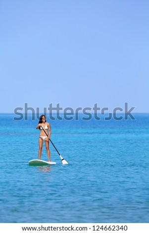 Hawaii beach lifestyle woman paddleboarding in bikini. Beautiful multiethnic woman surfing on stand up paddleboard on Big Island, Hawaii. - stock photo