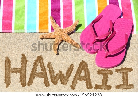Hawaii beach travel concept. Hawaii written in sand with water next to beach towel and summer sandals and starfish. Hawaiian vacation holidays photo. - stock photo