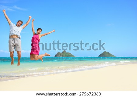 Hawaii beach Vacation. Happy couple tourists jumping. Young couple cheering for summer holidays showing success, happiness, and joy on Lanikai beach, Oahu, Hawaii, USA with Mokulua Islands. - stock photo