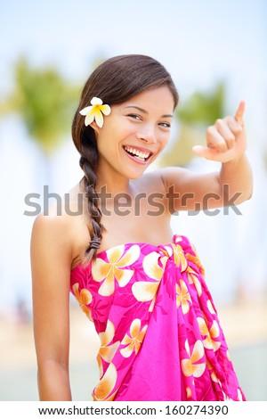 Hawaii beach woman making Hawaiian shaka hand sign. Pretty and free asian girl enjoying vacation holiday on beach resort with palm trees. Mixed race female on Big Island, Hawaii - stock photo