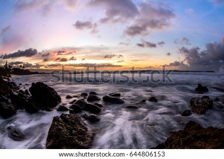Hawaii sunset over the ocean and rocks