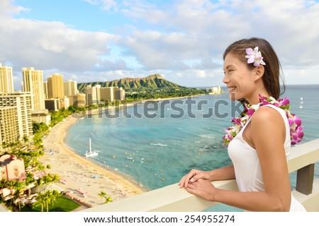 Hawaii Travel - Asian tourist on Hawaiian holidays looking at Waikiki beach and Diamond Head in the background, Honolulu City, Oahu, USA from hotel room in luxury resort. - stock photo