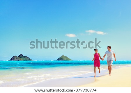 Hawaii vacation couple walking relaxing on white sand and pristine turquoise ocean water on Hawaiian beach Lanikai, Oahu island, USA. Holiday background with blue sky copy-space for travel concept. - stock photo
