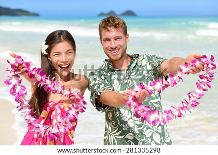 Hawaii welcome - Hawaiian people showing leis flower necklaces as a welcoming gesture for tourism. Travel holidays concept. Asian woman and Caucasian man on white sand beach in Aloha clothing. - stock photo