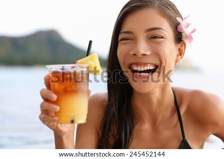 Hawaii woman drinking Mai Tai hawaiian drink. Asian tourist on holiday partying on Honolulu Waikiki beach, Oahu. - stock photo
