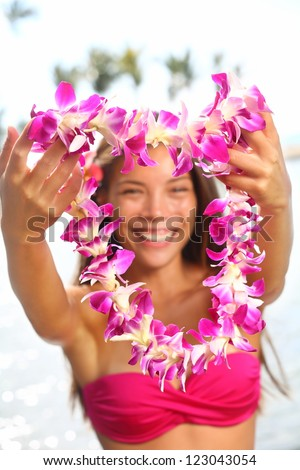 Hawaii woman showing flower lei garland of pink orchids. Beautiful smiling mixed race woman in bikini on beach giving a welcoming Lei on the hawaiian island Big Island. - stock photo