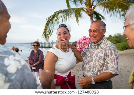 Hawaiian beach bride laughing it up with friends and family. - stock photo