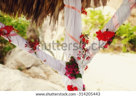 hawaiian decor with palm leaves and flowers in bungalow on the background of  the ocean and a beach, wedding ceremony in Seychelles