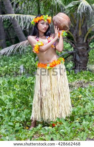 Hawaiian hula dancer with coconut. Woman in costume. Hawaiian hula dancer carries a large coconut. Hawaiian hula dancer on a green background holding coconut. Hawaiian hula dancer in nature with coconut.  - stock photo
