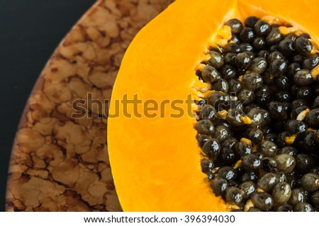 Hawaiian papaya fruit cut in half with seeds on a brown plate, dark background, close up - stock photo