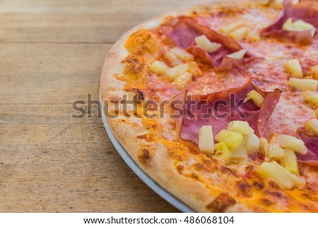 Hawaiian pizza on the white plate and wooden table