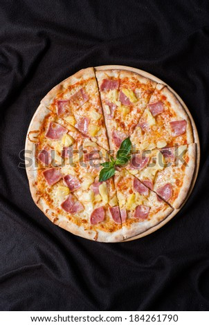 hawaiian Pizza , pineapple , ham and cheese on wooden table - stock photo