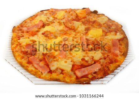 Hawaiian pizza topped with pineapple and ham on white background