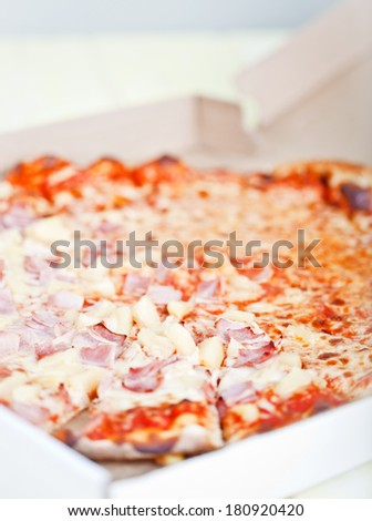 Hawaiian pizza with pineapple and ham in a box - stock photo