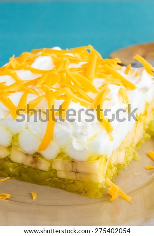 Hawaiian salad made with lemon jello, pineapple, banana, mini marshmallows, topped with whipped cream and cheddar cheese