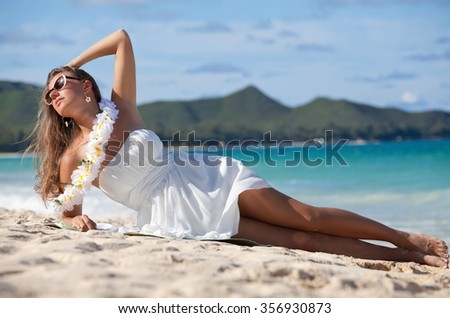 Hawaiian woman in white dress enjoying tropical beach and hawaiian summer vacation. Exotic travel vacations in Waimanalo beach, Oahu, Hawaii, USA.