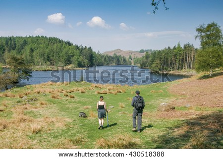 HAWKSHEAD, UK - MAY 8, 2006: Tourists enjoy a view of 'Tarn Hows' in the scenic English Lake District