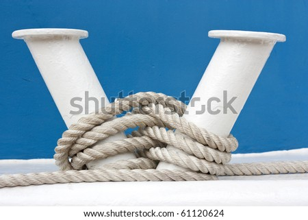 Hawser and white bollard on board of blue boat - stock photo