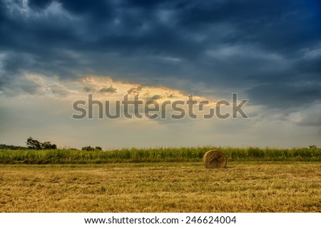 Hay bale in stormy clouds - stock photo