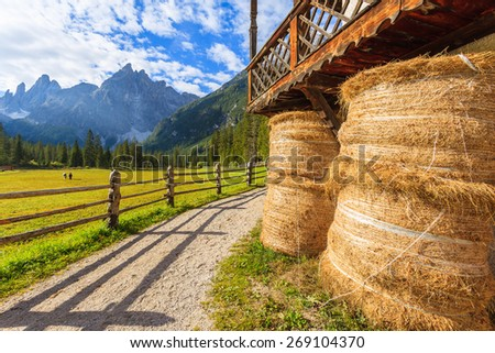 Hay bales and path along pasture in mountain valley of Fischleintal, Dolomites Mountains, South Tyrol, Italy - stock photo