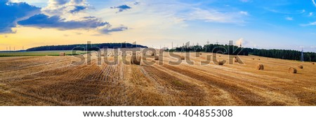 Hay bales on field. Autumn field with hay bales after harvest. Rural landscape with haystacks against the backdrop of a beautiful sunset sky. Panorama shot. - stock photo