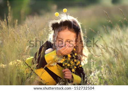 hay fever - little girl dressed as a bee - stock photo