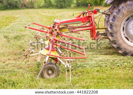 Hay spreader tool attached to the tractor, spreading hay on the field where it will dry  - stock photo