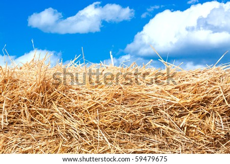 Hay stack detail. A close up of a haystack under the blue cloud sky. - stock photo