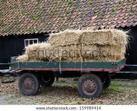 Hay wagon with stacked bales at a barn - stock photo
