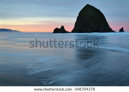 Haystack Rock, Cannon Beach, Oregon Sunrise. Sunrise at Haystack Rock in Cannon Beach, Oregon as the surf washes up onto the beach. United States.  - stock photo