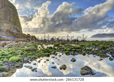 Haystack Rock with evening back lighting at low tide, Cannon Beach, Oregon. A large tide pool is in foreground with partly cloudy sky reflection. HDR fusion image. Warning sign on rock edited out.. - stock photo