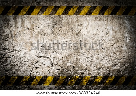 Hazard tape on blank dirty wall background with grunge and vignette tone - stock photo