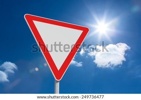 Hazard triangle against bright blue sky with clouds