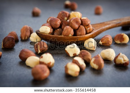 Hazel nuts, filberts, in wooden spoon on stone surface - stock photo