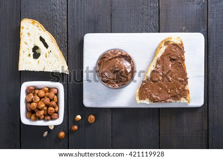 hazelnut cream sandwich breakfast and ingredients on white cutting board, black wooden table background - stock photo