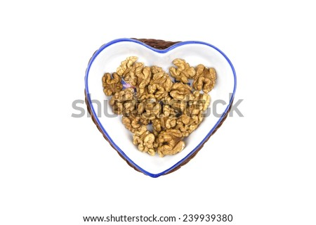hazelnut kernel on a porcelain dish in the shape of a heart, a healthy diet - stock photo