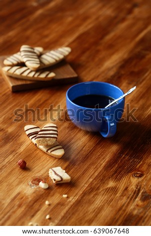 Hazelnut Long Cookies decorated with chocolate treads, blue cup of coffee, on wooden background.