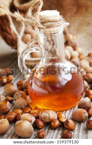 Hazelnut Oil Bottle With Hazelnuts and Kernels in the Background - stock photo