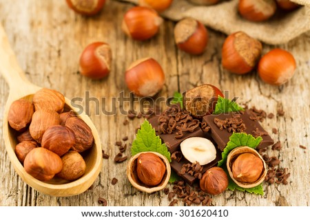 hazelnut with chocolate bars and green leaves on old wooden background - stock photo