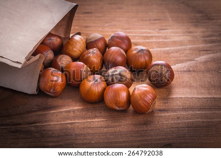 hazelnuts and paperbag on vintage wooden board food and drink still life  - stock photo